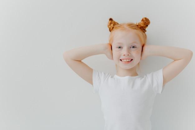 喜んで笑顔の女の子の屋内ショットは、手で耳をカバーし、ノイズを無視します