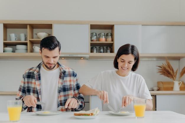 家族の夫婦がキッチンテーブルでポーズをとり、おいしい朝食をとり、その日の計画について話し、目玉焼きやハンバーガーを食べます