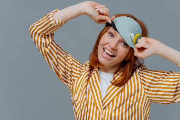 Довольная жизнерадостная женщина носит пижаму с завязанными глазами и в полоску