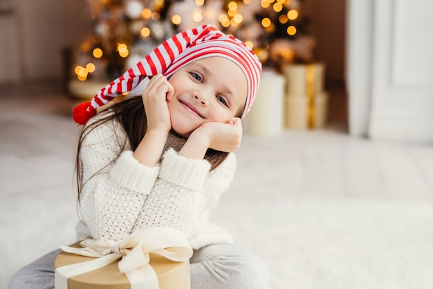 Красивый маленький ребенок позирует в гостиной, склоняется в настоящее время подарок, имеет счастливое выражение лица, рад получить сюрприз от родителей, проводит каникулы в кругу семьи. веселого рождества и счастливого нового года
