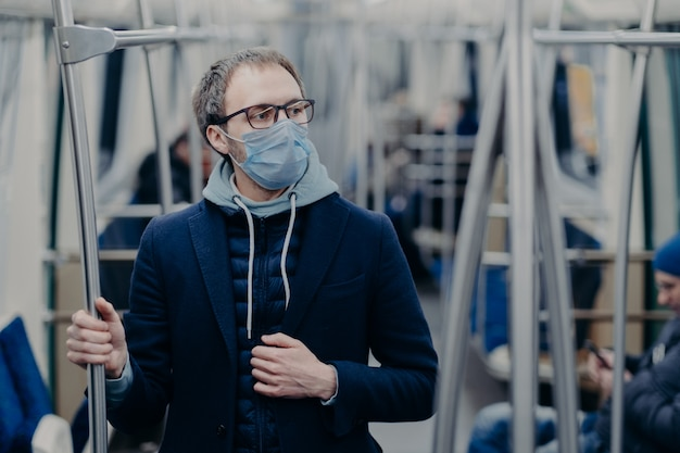 眼鏡の物思いにふける若者はコロナウイルスの発生中に保護手術用マスクを着用します。