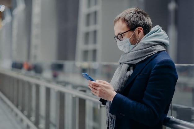 男性ブロガーの横ショットは、現代の携帯電話でテキストメッセージを送信し、フォロワーからのコメントを読み取り、コロナウイルスまたは他の感染症から身を守るために滅菌医療マスクを着用