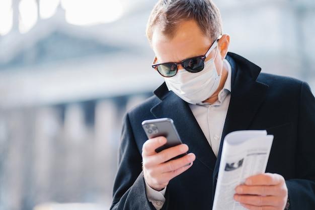 Открытый снимок серьезного менеджера, сфокусированного на сотовом дисплее, читает новости в интернете, держит газету, носит медицинскую маску для защиты от коронавируса, заражения вирусом гриппа, позирует на улице