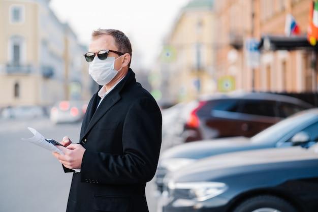 Вспышка пандемического коронавируса. серьезный бизнесмен позирует на улице возле транспорта на улице, держит современные сотовые и газеты, одетые в черное пальто, носит защитную маску от коронавируса.