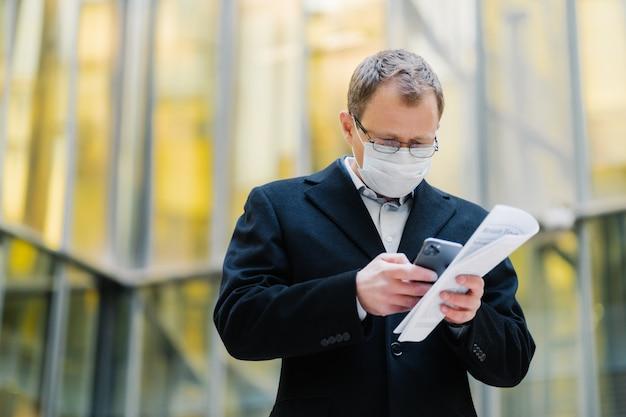 Концепция пандемии коронавируса. фотография мужчины-менеджера, сфокусированного на устройстве смартфона, отправляющего текстовые сообщения, в очках и медицинской маске, держит документы, гуляет по улице во время карантина, пандемии