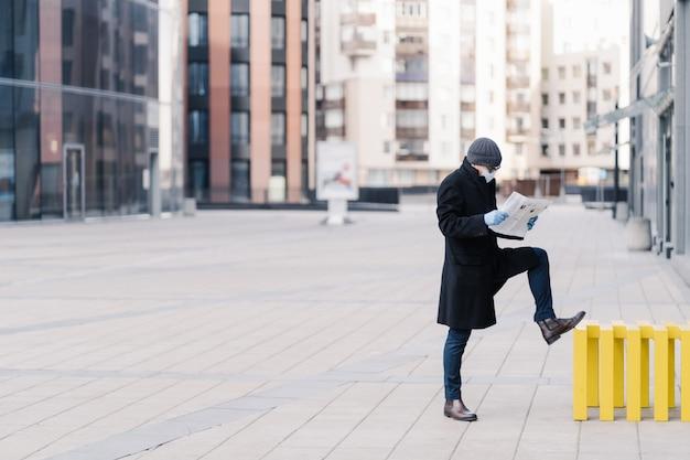 ビジネスマンの水平ショットはオフィスビルの近くに屋外に立ち、新聞を読み、検疫中に医療用マスクと手袋を着用し、コロナウイルスを防ぎます。全世界のパンデミック状況。