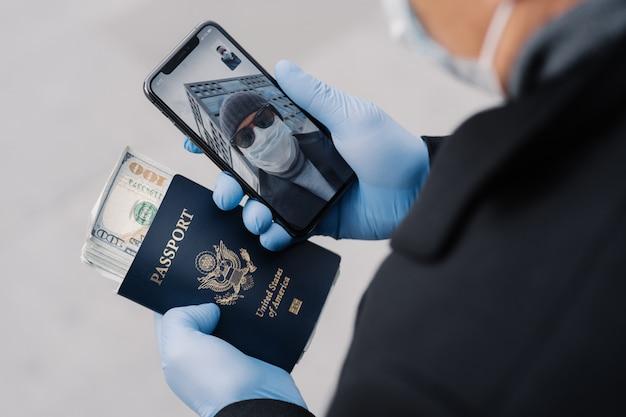 Онлайн общение, карантин и концепция социального дистанцирования. неизвестный мужчина держит мобильный телефон, проводит видеоконференцию с другом, несет паспорт и много денег, заботится о здоровье, носит маску