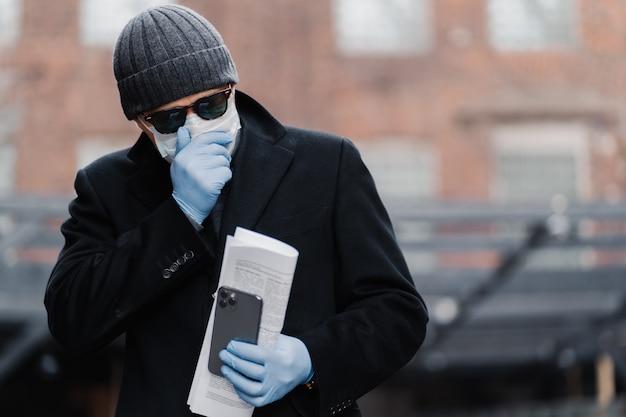 人の咳の屋外でのショット、コロナウイルス感染を広めようとしない、防護マスクと手袋を着用する、新聞と携帯電話を持っている、肺炎がある、呼吸に問題がある。ウイルス防止。