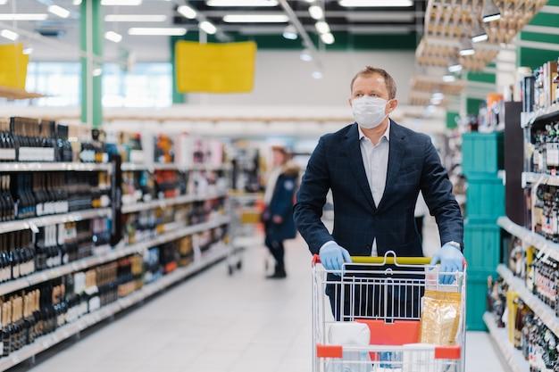 Фотография взрослого мужчины носит одноразовую маску, делает покупки, думает о защите и предотвращает меры во время вспышки коронавирусной пневмонии, позирует с тележкой в универмаге. эпидемическое время
