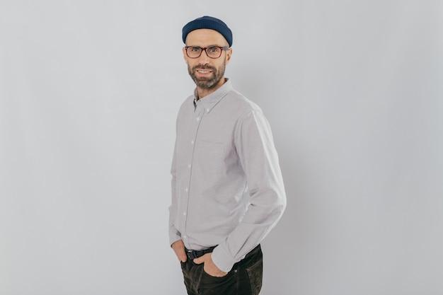 フォーマルな服を着た魅力的な無精ひげを生やした男は、光学メガネ、白い背景の上のモデルを着ています。