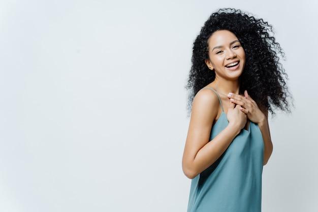 Обрадованная афро американка позитивно смеется, держит руки на груди, слышит веселую шутку, выражает счастье