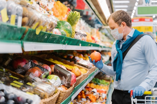 男の横向きのショットは、コロナウイルスの発生中に免疫力を高めるために新鮮な果物を選ぶ