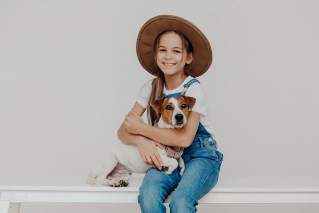 ファッショナブルな服を着た愛らしい小さな幼児少女、ジャックラッセルテリア犬を抱擁します。