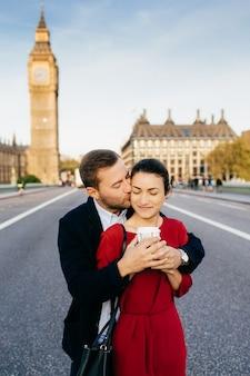 愛情深い男性と女性がお互いを受け入れ、キスし、ビッグベン近くのロンドンで休暇を過ごす