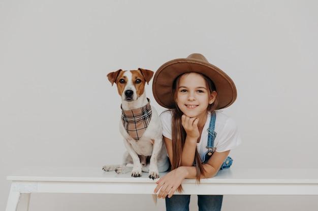 コンテンツのかわいい女の子は帽子をかぶって、白いテーブルに寄りかかって、血統の犬の近くでポーズします