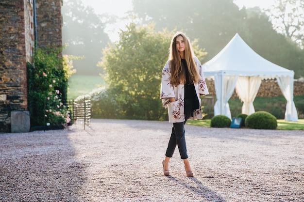 Портрет стройной высокой женщины в накидке и на высоких каблуках