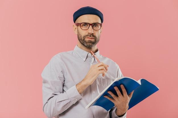 魅力的な若い男性は教科書を保持し、正式に服を着て、主催者でメモを作ります。