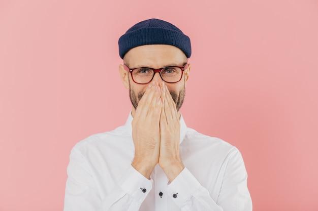 ポジティブな嬉しい男性はポジティブな感情を表現し、両手で口を覆い、静かに笑い、ヘッドギアを着用