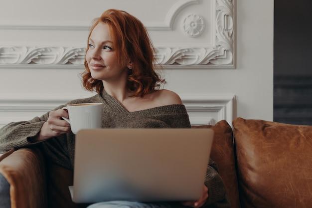 Крытый выстрел довольной рыжей женщины работает фрилансером на ноутбуке