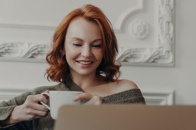 Красивая рыжеволосая женщина наблюдает за тренировочным вебинаром на ноутбуке,