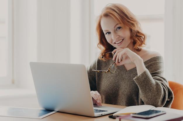 満足している女性科学者がラップトップコンピューターの研究を行い、コワーキングスペースでポーズをとる
