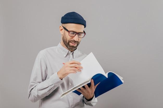ハンサムな無精ひげを生やした若い男はノートを保持し、ページをめくる