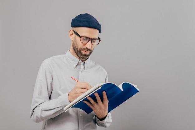 深刻な男性教師は次のクラスのメモを書き留め、メモ帳を保持