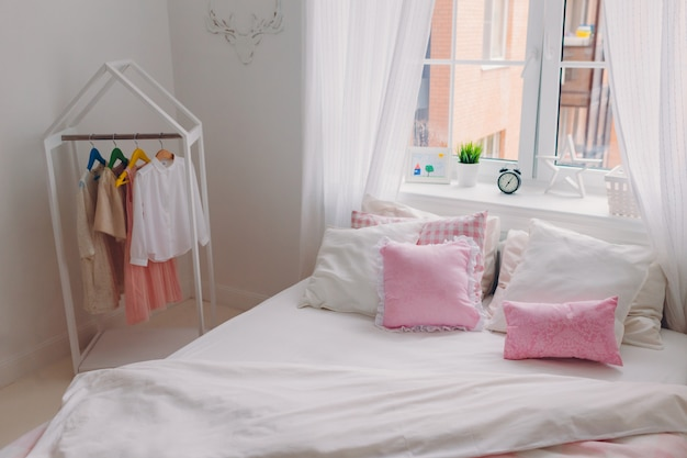 大きなベッド、ハンガーの服、白いカーテンと窓と空の居心地の良い広々としたベッドルームの写真