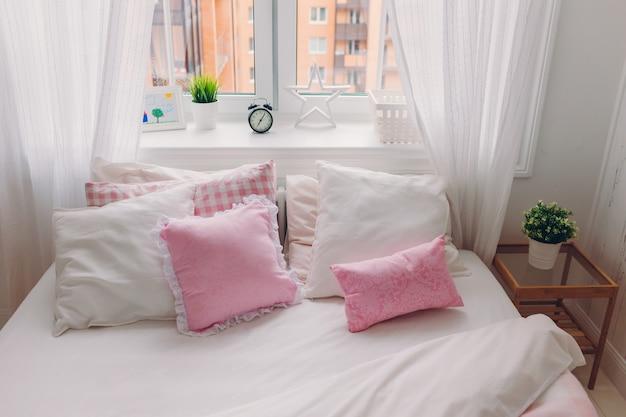 白い寝具、柔らかい枕、緑の植物の窓、目覚まし時計、写真付きのベッド