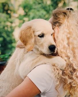 巻き毛の女性は、お気に入りの血統犬と夏の散歩を屋外