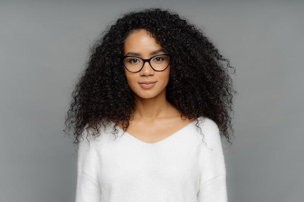 黒い肌、アフロのふさふさした髪の深刻な女性は大きな透明なメガネと白い柔らかいセーターを着ています。