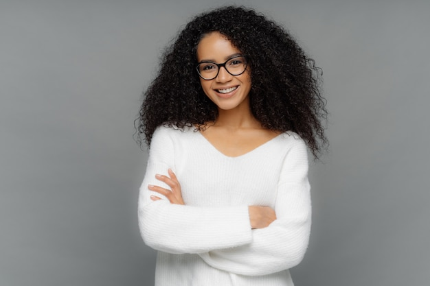 カールを持つ美しいアフリカ系アメリカ人女性、穏やかな笑顔を持っている、手を交差させ続ける