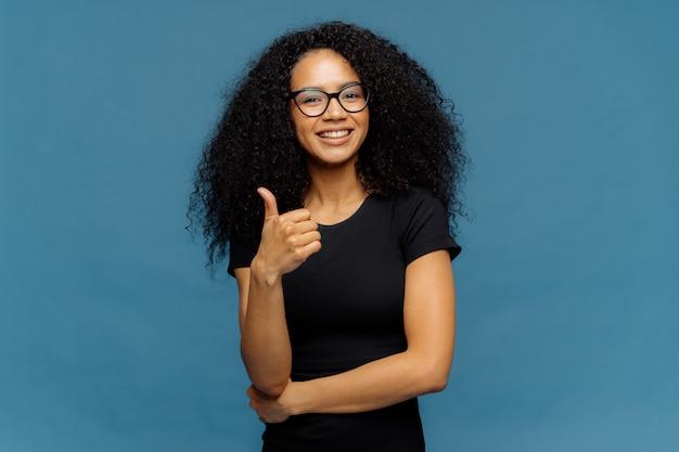 素敵な黒い肌の女性はジェスチャーのようになり、親指を立て続け、良いものを承認します