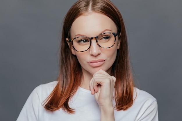 完全な唇、暗い茶色の髪の思慮深い女性は、白い服を着て、思慮深く脇に見える