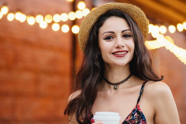黒い長い髪、ハシバミの目、赤い唇、ネックレス、夏の帽子、楽しい表情のドレスを着た若い女性モデル