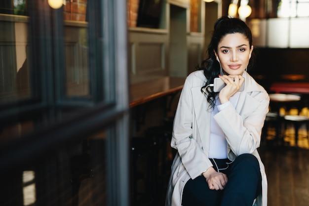 黒い髪と良いトラックを楽しんで居心地の良いカフェに座っているスタイリッシュな白い服を着ている赤いマニキュアの魅力的な女性