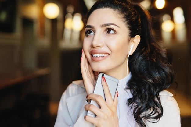 ファッションライフスタイルコンセプト。音楽を聴く魅力的な笑顔を持つポニーテールでかわいい女性の肖像画