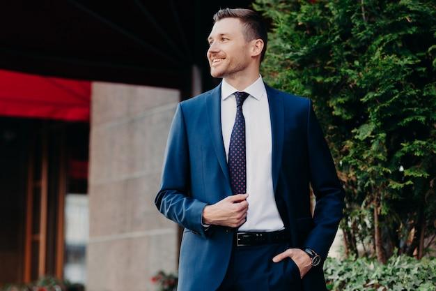 フォーマルなスーツを着た男は、ポケットに手を入れ、積極的に脇に見え、銀行の近くに立っている