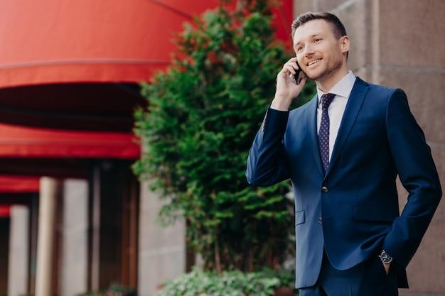 フォーマルなスーツの男性エグゼクティブ、スマートフォンを介して電話での会話