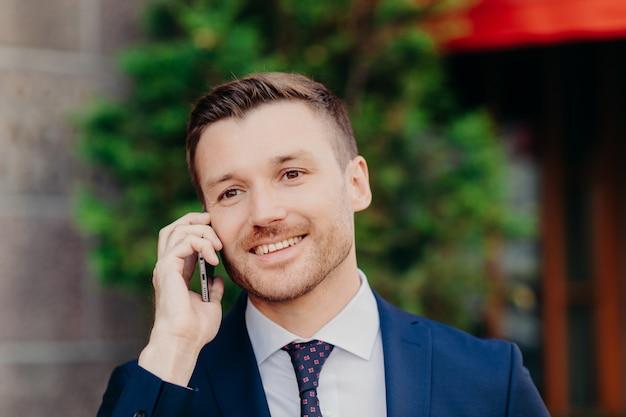 男性はフォーマルな服を着て、携帯電話でビジネスに関する会話をしています