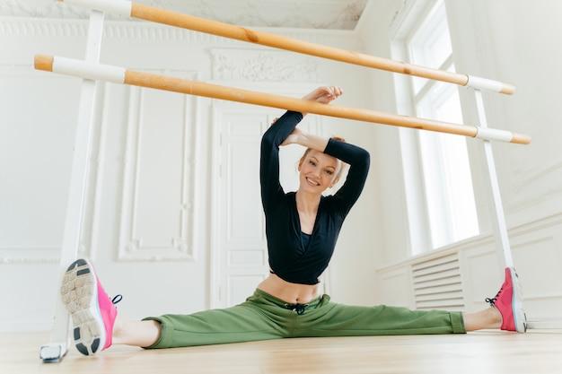 バレエダンサーは脚の分割を示し、アイコンタクトを持ち、バレに近いポーズをとり、ダンススタジオでリハーサルします