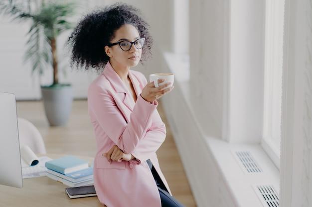 思慮深い巻き毛の若い女性が一杯のコーヒーを保持します