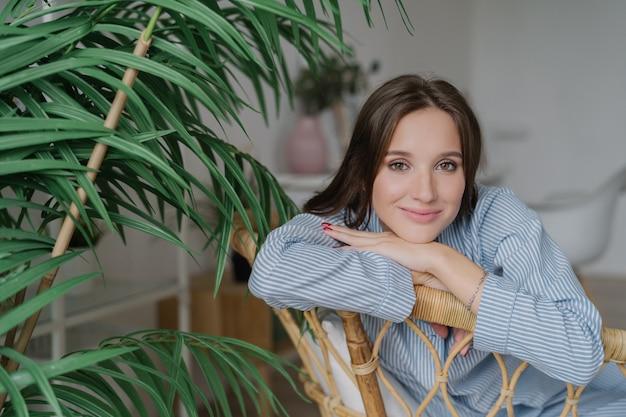 Красивая европейская женщина, одетая в стильную одежду, сидит на деревянном стуле возле зеленого растения
