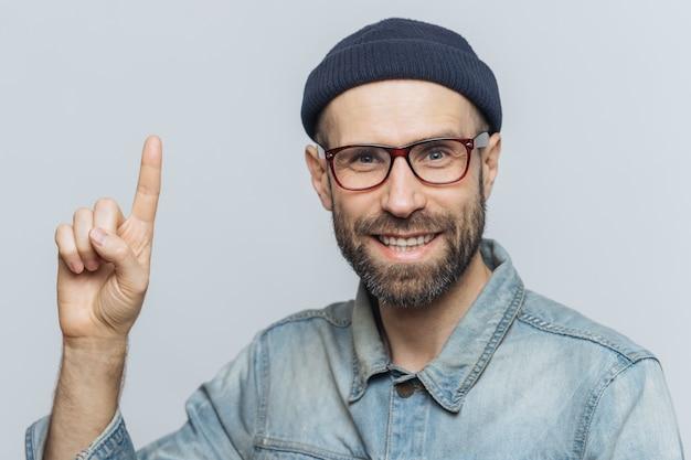 Позитивный красивый бородатый кобель поднимает передний палец, смотрит с веселым выражением лица