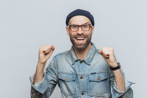 大喜びの男性は彼の成功を喜ぶ、拳を握り締める、うれしそうに見える