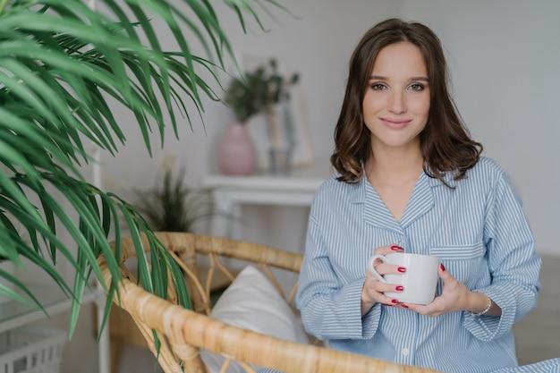 夜の衣装に身を包んだ女性は、コーヒーや紅茶のカップを保持しています