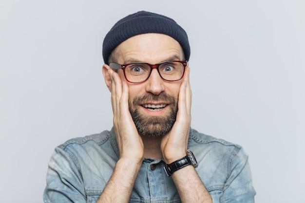 Крытый снимок возбужденного бородатого мужчины с голубыми глазами и веселым выражением, держит руки на щеках