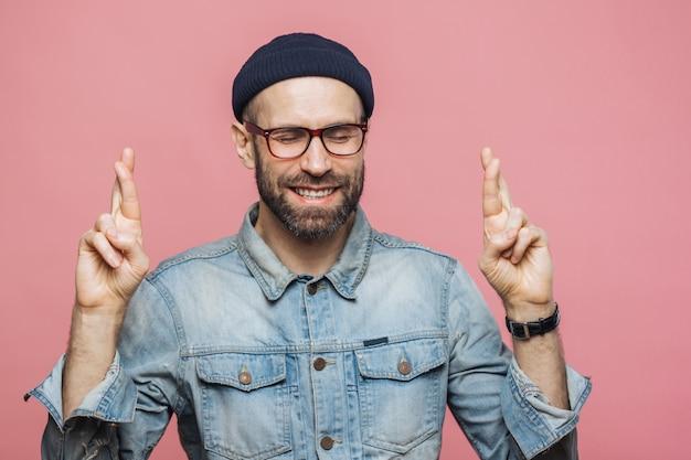 ハンサムな無精ひげを生やした男性の屋内ショットは、指を交差させ、目を閉じ、幸せな表情を保ちます