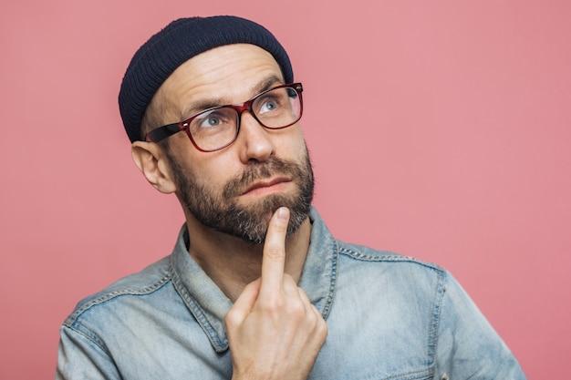 思慮深い表情で快適な探しているひげを生やした男性のショットを閉じる、あごに指を保ちます