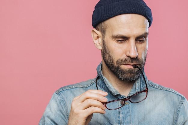 物思いにふけるひげを生やした男のヘッドショットは思慮深く見下ろし、メガネを保持し、デニムジャケットを着ています。